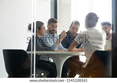 Serious young diverse team discussing work moments, startup ideas during brainstorming meeting with client or interviewing new employee. Confident male leader pays attention to important job tasks.