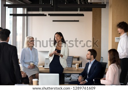 Serious young female asian coach mentor team leader speaking at diverse corporate group meeting talking to office workers at lecture training teaching explaining presenting new business plan