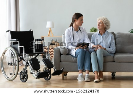 Serious young female doctor comforting injured disabled handicapped senior lady patient tell diagnosis help old grandma with disability problem talk at medical checkup visit with wheelchair at home