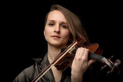 Serious young female violinist or musician playing on an antique Baroque violin during a classical music performance in a head and shoulders frontal portrait on black