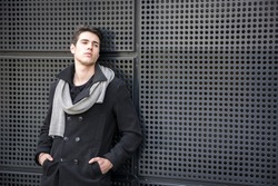 Serious Young Handsome Man in Winter Outfit Leaning on a Metal Wall While Looking to the Right of the Frame at Large Copyspace
