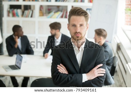 Serious young leader in suit looking at camera standing arms crossed on executive team meeting background, confident manager boss ceo co owner posing in front of partners group, headshot portrait