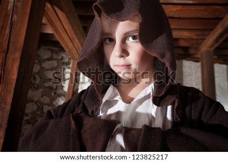 Serious young magician with folded arms hidden in his cloak