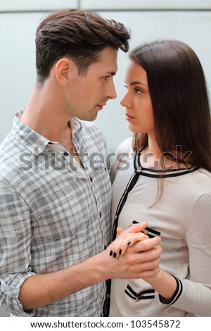 Serious young man and woman hold hands and look at each other