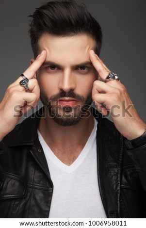 serious young man focuses his mind , portait on grey background #1006958011