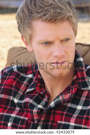 serious young man in plaid shirt sitting outdoors