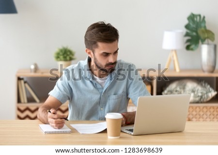Serious young man looking at laptop making notes working with documents, doing paperwork, online research, focused male student studying in internet writing down information in notebook, e-learning