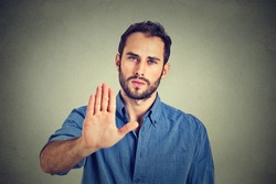 Serious young man showing stop gesture isolated on gray wall background