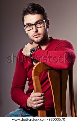 serious young man, sitting in his chair and stares