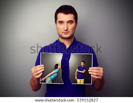 serious young man tearing the photo of couple