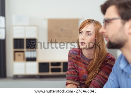 Serious Young Office Man and Woman, Sitting at the Office, Looking to the Left of the Frame Together