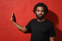 Serious young protester african american man with dreadlocks 20s wearing casual black t-shirt posing showing stop gesture with palm aside isolated on bright red color wall background studio portrait