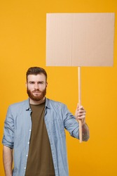 Serious young protesting man guy hold in hand protest sign broadsheet blank placard on stick isolated on yellow wall background studio portrait. Protests strikes pickets concept. Youth against city