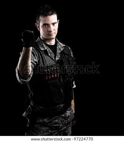 serious young soldier tightening the fist on a black background