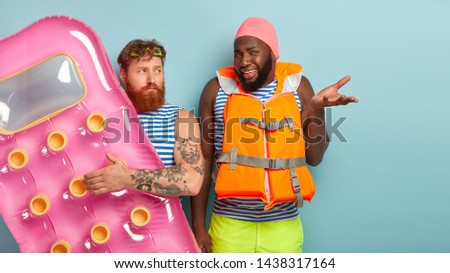 Serious young unshaven man with foxy hair, holds inflated big mattress, puzzled dark skinned guy raises palm, wears lifejacket and swimhat, ready for summer rest during hot day, going on beach #1438317164