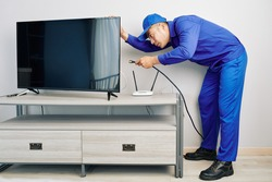 Serious young Vietnamese repairman installing tv set in apartment of customer