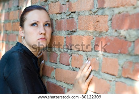 Serious young woman in black dress standing by a brick wall