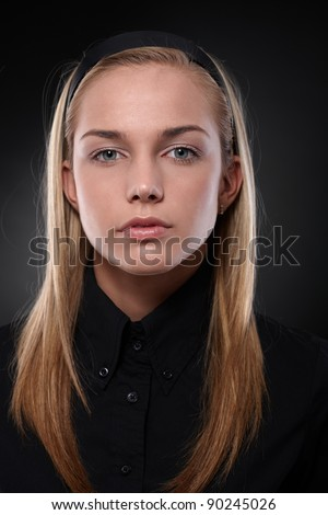 Serious young woman in black, looking at camera, closeup portrait.?
