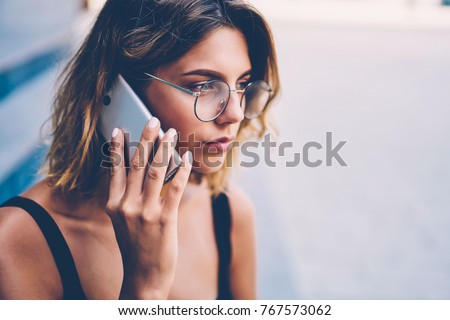 Serious young woman in trendy eyewear concentrated on information getting during phone talk with customer support operator, thoughtful hipster girl calling to friend standing near publicity area