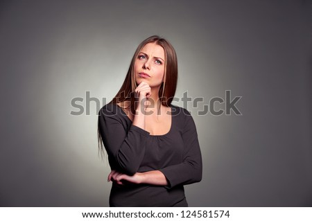 serious young woman pondering over something. studio shot against dark grey background
