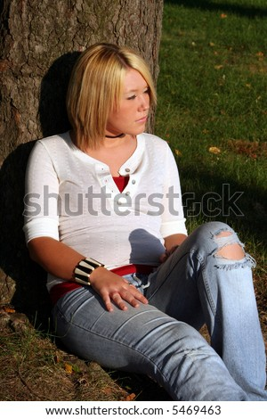 Serious young woman sitting on the ground near a tree, with her face turned to her left toward the sunlight.