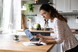 Serious young woman wearing glasses calculating finances, household expenses, confident businesswoman working with project statistics, using laptop and calculator, standing in kitchen at home
