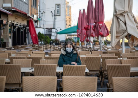 Serious young woman with protective face mask sitting outdoors at the empty cafe terrace  during the coronavirus outbreak in Cologne, Germany