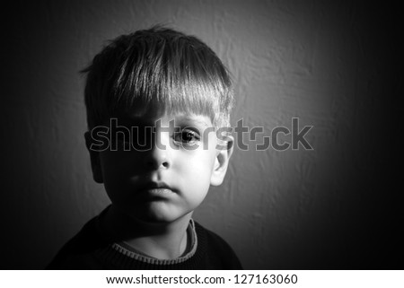 seriouse little boy looking to the camera, black and white