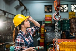 seriously components factory female staff hold helmet focus on looking at chain cranes and through remote control  adjust for delivery finished products.