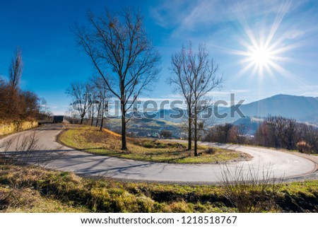 serpentine in beautiful mountainous countryside. sunny november day. tall leafless trees along the road. village down in the valley #1218518767