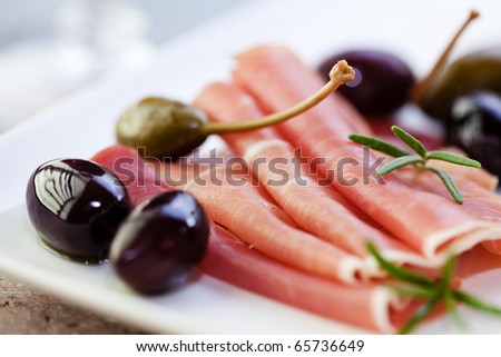Serrano ham with black olives and caper berries