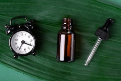 Serum bottle and alarm clock on the green leaf. Flat lay. Skincare routine and anti-aging products concept