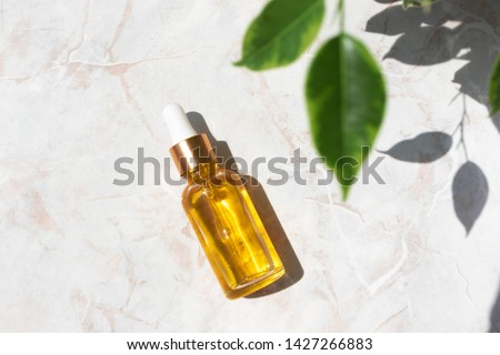 Serum in glass bottle on marble background. Aromatherapy oil, concept of natural cosmetic