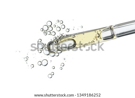 Serum in pipette isolated on white background. Cosmetic liquid dropper with bubbles top view.