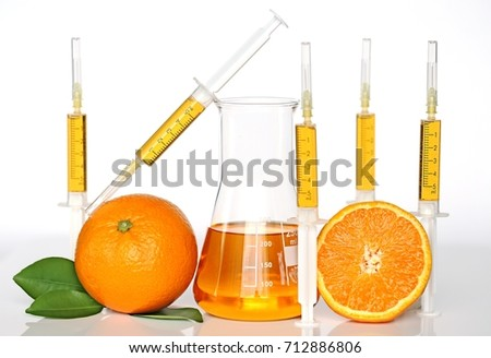 Serum with vitamin C. Vitamin C in syringes and in a medical flask and orange on a light background #712886806