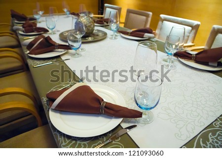 Served cutlery sets, plates, napkins, empty wine glasses, on tables in a restaurant interior - stock photo