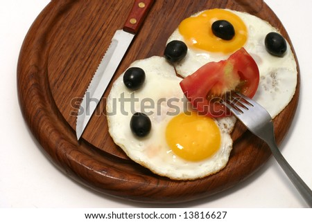 served fried egg on wooden plate with olives