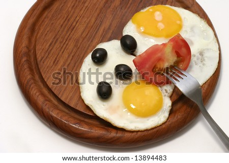 served fried egg on wooden plate with tomato and olives
