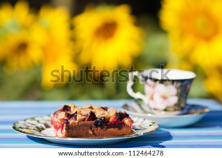 served garden table with plum streusel cake and coffee and luminous sunflowers in the background