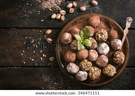 Served homemade chocolate pralines in the plate on wooden background
