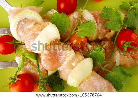 served raw chicken kebabs with tomatoes and peppers
