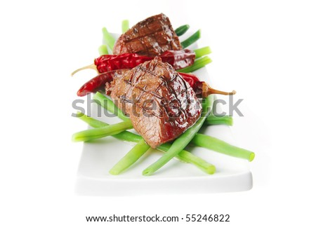 served roast veal fillet on a white plate with peppers