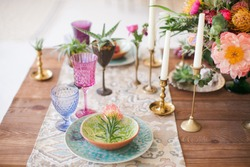 Served table for a wedding dinner in boho chic style. Decor from fresh flowers of peonies, roses, orchids and Leucospermum conocarpodendron. Crockery plates, glasses and candles. Wooden table.