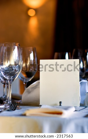 Served table in restaurant interior, with blank menu, with copy space - stock photo