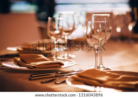 served table with white tablecloth. white plates, wine glass, fork, knife #1316043896