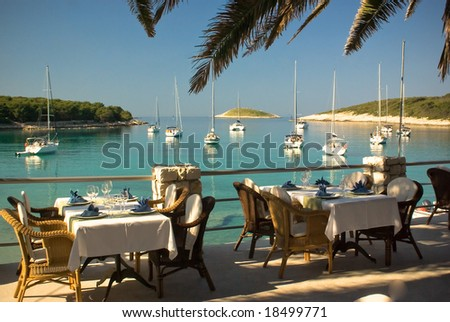 Served tables at yachting club beach restaurant