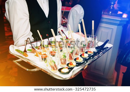 Server holding a tray of appetizers at a banquet. Toned image instagram style