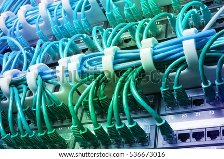Server rack with blue internet patch cord cables connected to patch panel in server room. Gradient #536673016