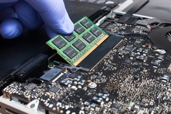 Service engineer install new RAM memory chips to the laptop. Repairing and upgrading laptop concept. Close up view.
