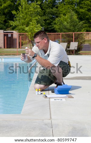Service man checking chlorine, PH and other chemical levels in community pool